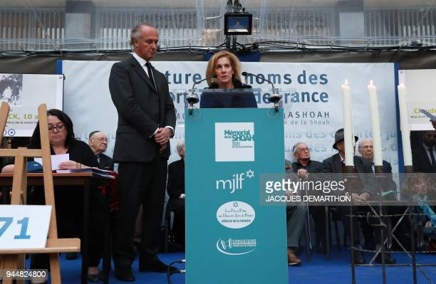US Ambassador to France Jamie McCourt reads out names of World War II deported jews flanked by Shoah Memorial vicepresident Francois Heilbronn during...