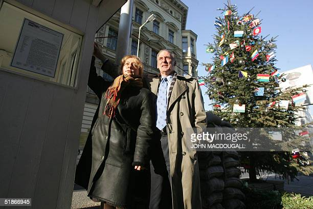 US ambassador to Germany Daniel Coats and Alexandra Hildebrandt director of the House at Checkpoint Charlie Museum pose as they light up the...
