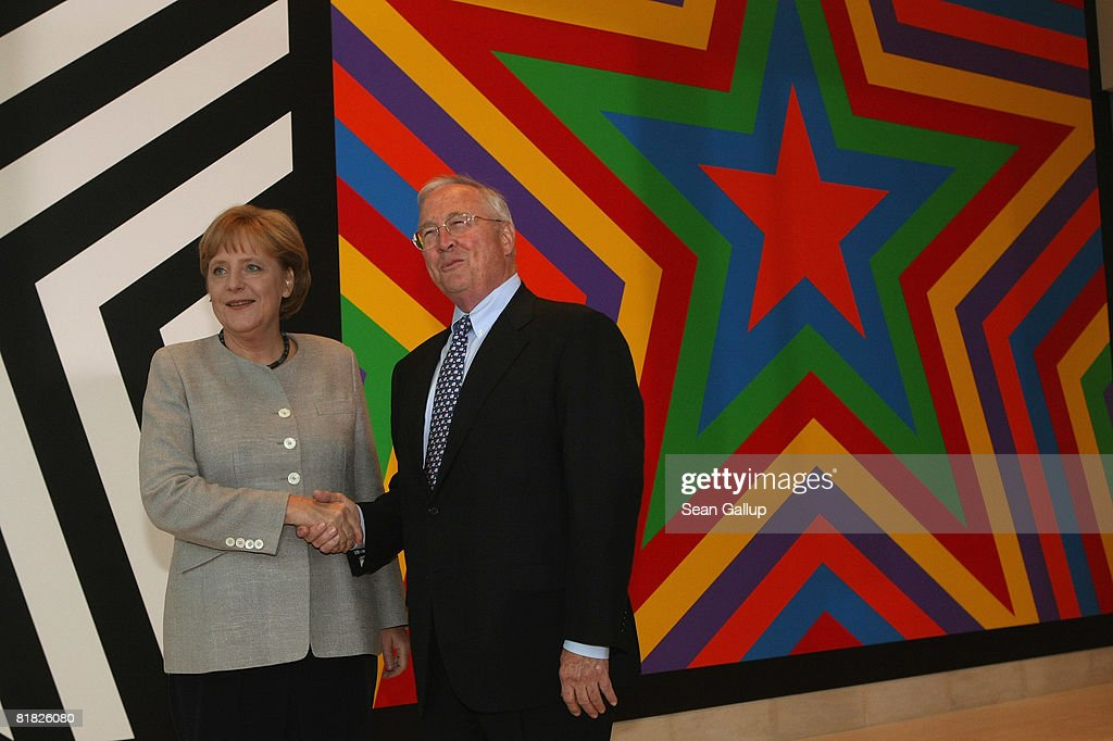 U.S. Ambassador to Germany William Timken (R) greets German Chancellor Angela Merkel during the official opening ceermony of the new U.S. embassy on July 4, 2008 in Berlin, Germany. Architectural critics claim the embassy, designed by American architect Moore Ruble Yudell, offers little in architectural innovation or design.
