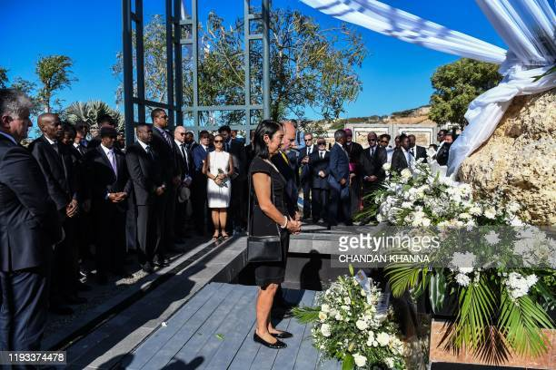US Ambassador to Haiti Michele Sison along with Assistant Administrator for USAID John Barsa offer flowers at the mass graveyard during the...