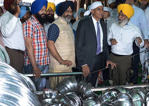 US Ambassador to India Richard Rahul Verma speaks with officials as he views piles of utensils at a community kitchen inside the Sikh Shrine The...