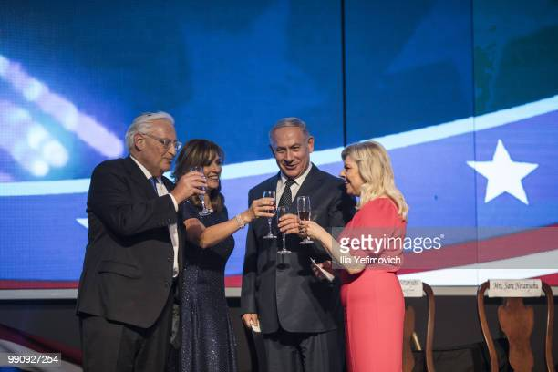 US ambassador to Israel David Freedman and Israeli Prime Minister Benjamin Netanyahu drink champagne with their wives after a speech at a 4th of July...