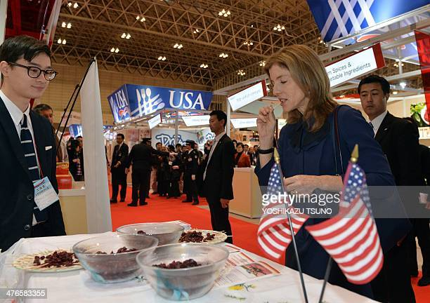 US Ambassador to Japan Caroline Kennedy tastes dried cramberry as she inspects the US booth at the annual 'Foodex' food exhibition in Chiba suburban...