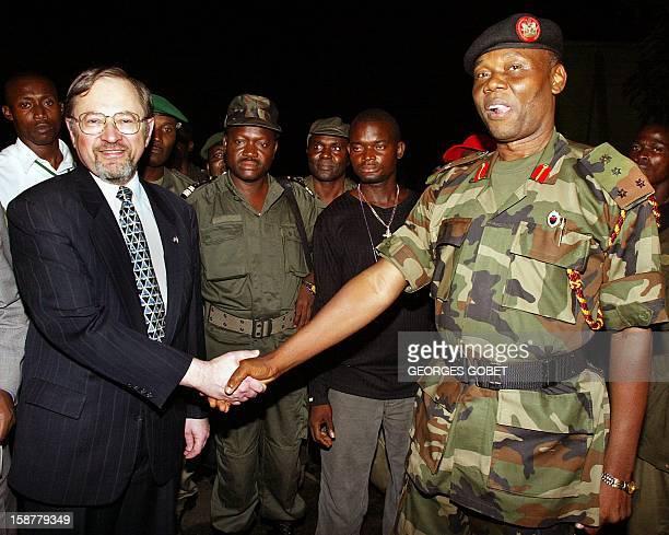 US ambassador to Liberia John Blaney shakes hands with Nigerian General Festus Okonkwo 30 July 2003 at Robert Field International Airport in Monrovia...