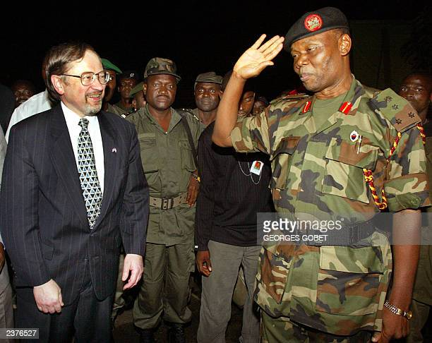 US ambassador to Liberia John Blaney smiles as Nigerian General Festus Okonkwo salutes 30 July 2003 on his team's arrival at Robert Field...
