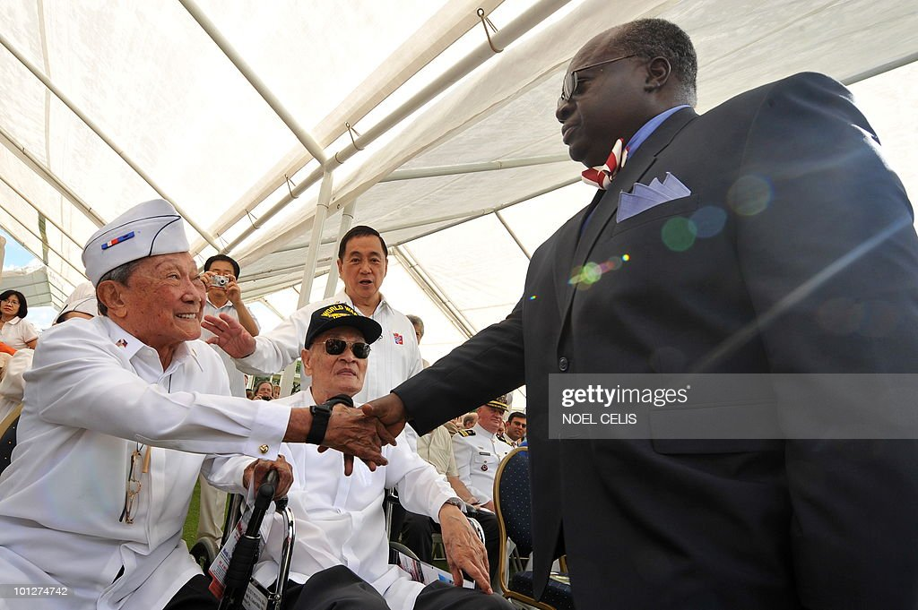 US Ambassador to the Philippines Harry Thomas (R) shakes hands with a Philippine war veteran during a service to mark US Memorial Day and honour soldiers who fell during World War II at the Manila American Cemetery in Fort Bonifacio, Manila on May 30, 2010. At least 17,000 graves lay in the memorial park that pays tribute to US and Philippines soldiers that fought side by side during World War II.