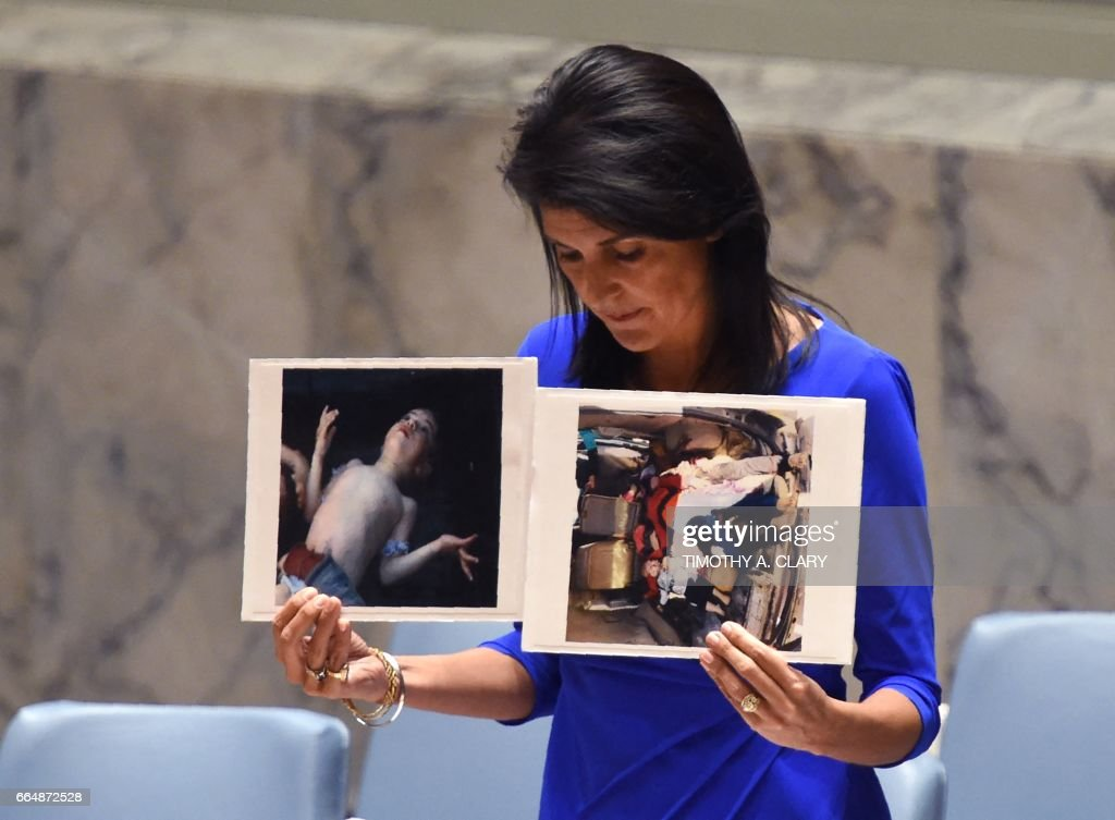 US Ambassador to the UN, Nikki Haley holds photos of victims as she speaks as the UN Security Council meets in an emergency session at the UN on April 5, 2017, about the suspected deadly chemical attack that killed civilians, including children, in Syria. /