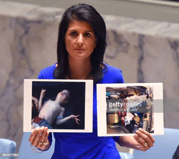 US Ambassador to the UN Nikki Haley holds photos of victims as she speaks as the UN Security Council meets in an emergency session at the UN on April...