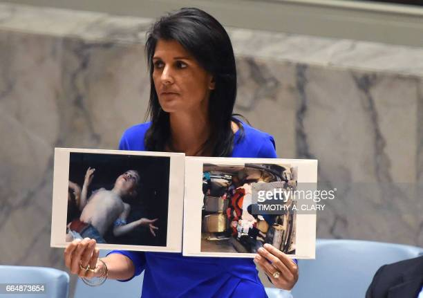 Ambassador to the UN Nikki Haley holds photos of victims as she speaks as the UN Security Council meets in an emergency session at the UN on April 5...