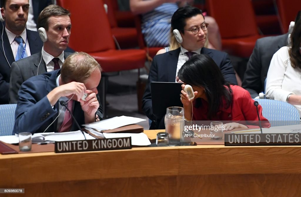 US Ambassador to the United Nations Nikki Haley (R) confers with Britain's Ambassador Matthew Rycroft (L) during a Security Council meeting on North Korea at the UN headquarters in New York on July 5, 2017. The United States will present to the UN Security Council a new draft resolution imposing sanctions on North Korea after it launched its first intercontinental ballistic missile, Haley said. / AFP PHOTO / Jewel SAMAD
