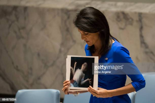S Ambassador to the United Nations Nikki Haley holds a photo of a victim of the Syrian chemical attack during a meeting of the United Nations...