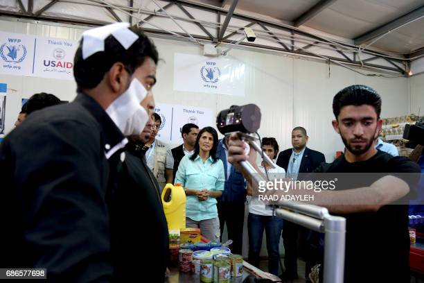 US Ambassador to the United Nations Nikki Haley looks on as a bandaged Syrian refugee has his iris scanned at a supermarket on May 21 2017 in Zaatari...