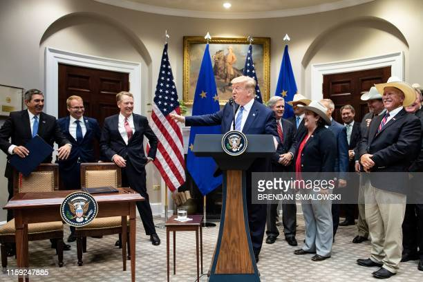 Ambassador to the US Stavros Lambrinidis and others react as US President Donald Trump makes a joke about tariffs on European car makers during an...