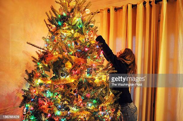 Amber Click puts an ornament on a Christmas tree completely void of any presents at her family's foreclosed home on December 23 in Dale City VA Bank...