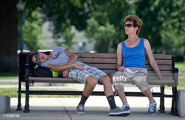 Amber Dominguez and her mother Donna take cover from the sun on shaded benches near the House steps