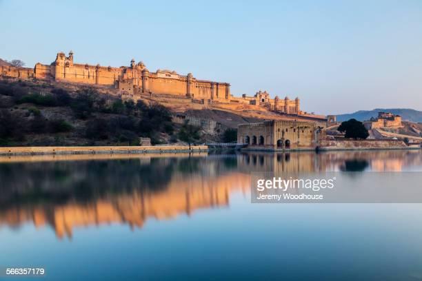 amber fort reflecting in still river under blue sky, jaipur, rajashan, india - amber fort stockfoto's en -beelden