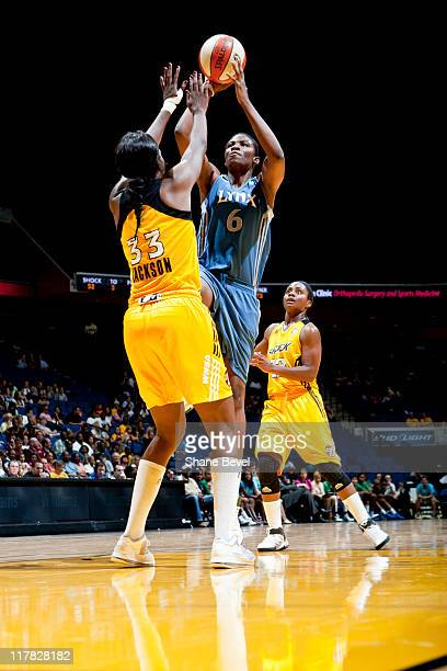 Amber Harris of the Minnesota Lynx fires a shot from the paint over the head of Tiffany Jackson while Ivory Latta of the Tulsa Shock watches during...