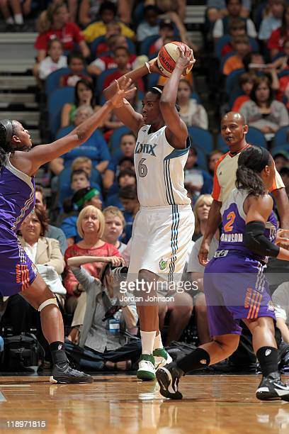 Amber Harris of the Minnesota Lynx looks to move the ball against Kara Braxton of the Phoenix Mercury during the game on July 13 2011 at the Target...
