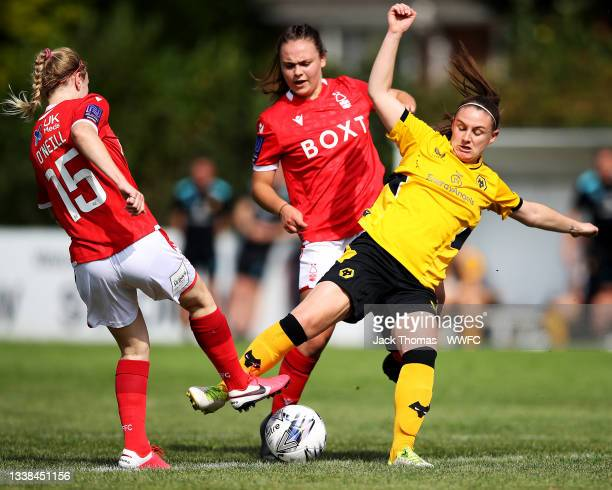 Amber Hughes of Wolverhampton Wanderers is challenged by Olivia Cook and Laura-Jayne O'Neill of Nottingham Forest Women during the FAWNL Northern...