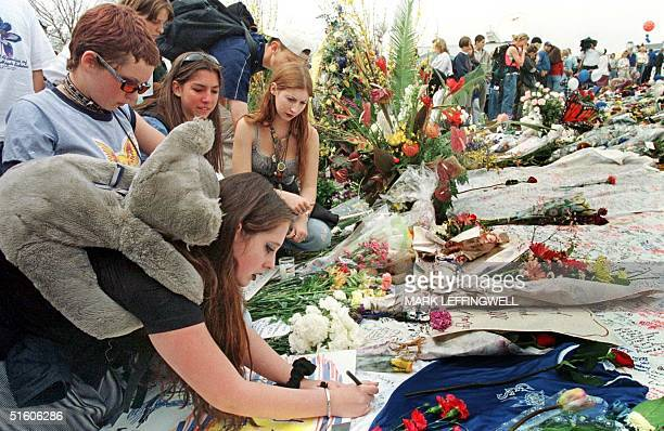Amber Johnson writes a note for the Columbine High School shooting victims with friends Jessi Wilson Kira Osado and Krystal Osado 26 April 1999 at...