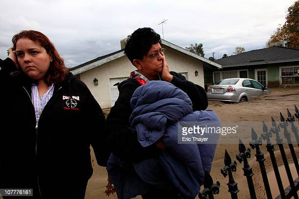 Amber Mortan and her mother Monica Mortan react after returning to their flooded home December 23 2010 in Highland California Residents throughout...