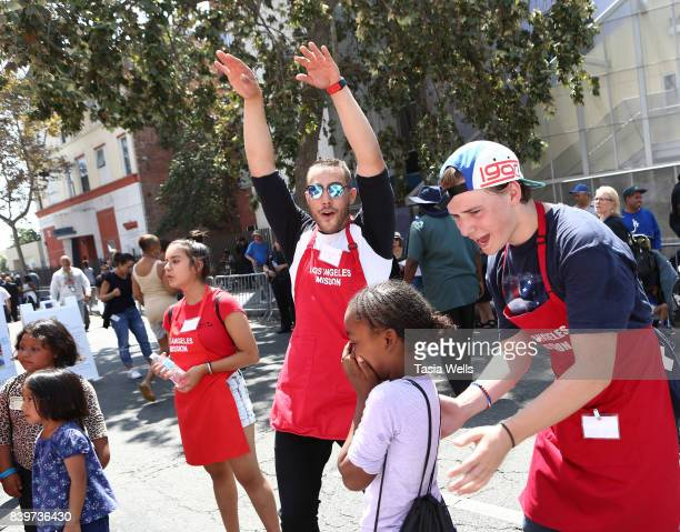 Amber Romero Lucas Lockwood and CJ Valleroy volunteer at the Los Angeles Mission's End of Summer Arts and Education Fair at Los Angeles Mission on...