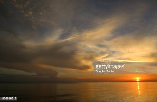 amber sky over the ocean - deep sea fishing stock photos and pictures