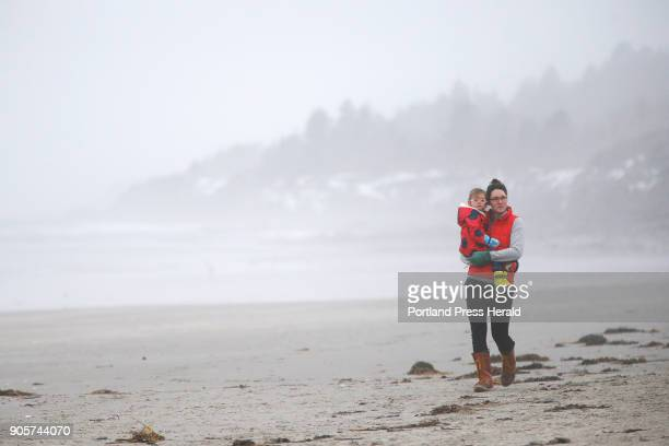 Amber Stewart of Gorham walks along Higgins Beach with 2yearold daughter Leah on a foggy Friday morning 'It's so warm that we had to get outside'...