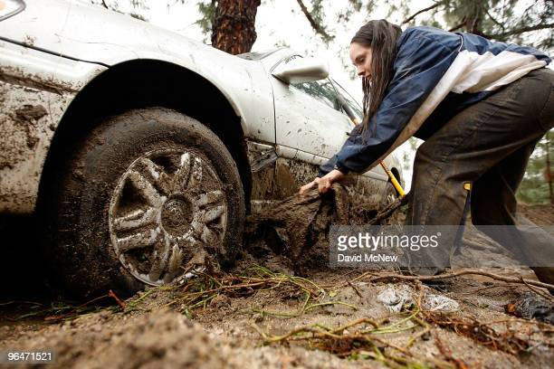 Amber Vos pulls on debris as she tries to dig out her car that was swept away after heavy rains caused mudslides on February 6 2010 in La Canada...