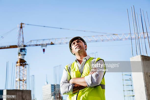 Ambitious architect standing arms crossed at site