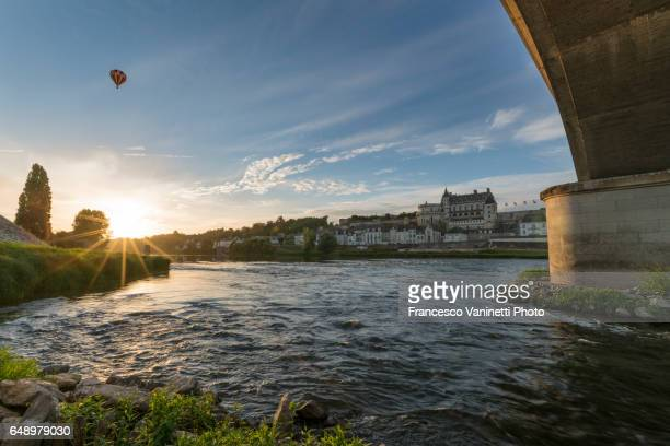 Amboise with a hot-air balloon in the sky from under the bridge.