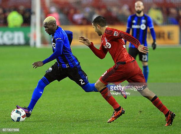 Ambroise Oyongo of Montreal Impact dribbles the ball past Steven Beitashour of Toronto FC during the second half of the MLS Eastern Conference Final...