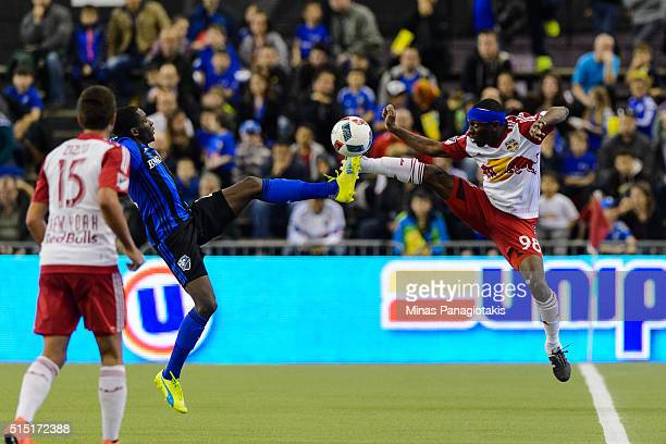 Ambroise Oyongo of the Montreal Impact and Shaun WrightPhillips of the New York Red Bulls kick the ball during the MLS game at the Olympic Stadium on...