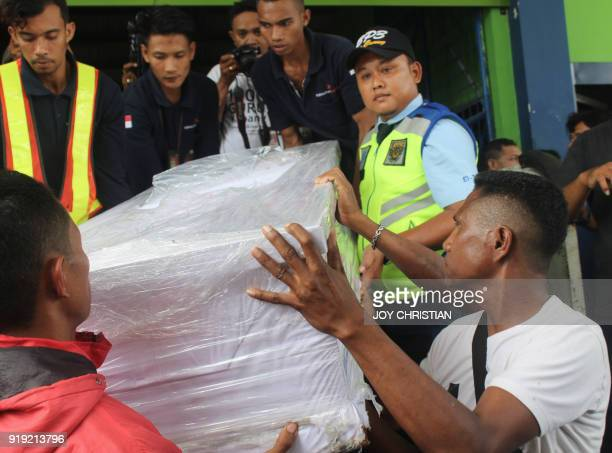 Ambrosius Koa a relative of overseas worker Adelina Sau a domestic helper who died in Malaysia helps airport officials unload her coffin during its...