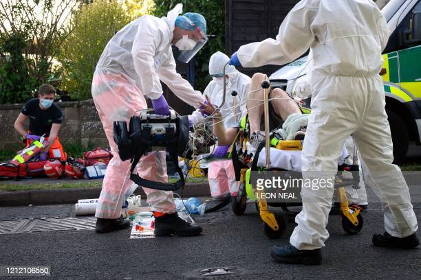 TOPSHOT Ambulance and air ambulance crews wearing personal protective equipment work to stabilise a patient with possible COVID19 symptoms who was...