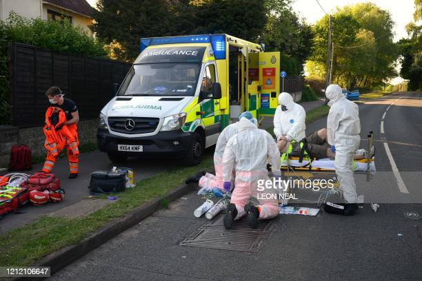 Ambulance and air ambulance crews wearing personal protective equipment work to stabilise a patient with possible COVID19 symptoms who was found...