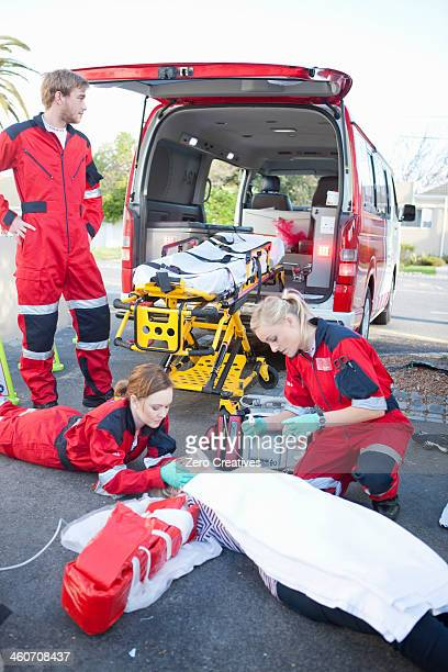 Ambulance and paramedics attending patient on road