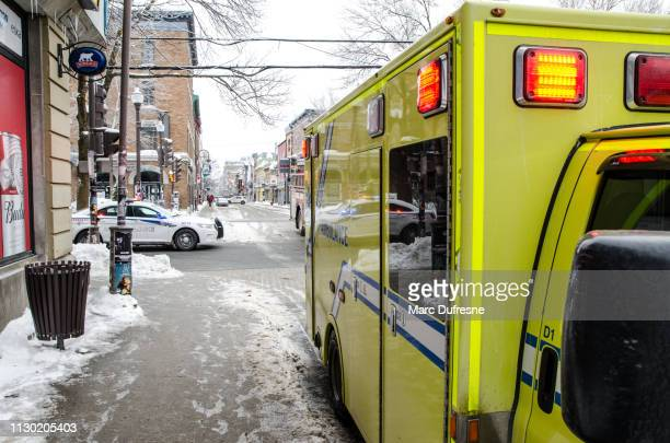 ambulance and police car in street during winter day - quebec stock pictures, royalty-free photos & images