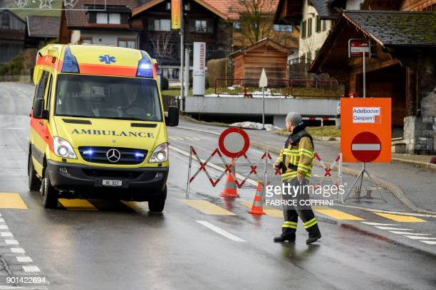 A ambulance crosses a check point to access the closed road leading to the Adelboden FIS Alpine Ski World Cup races after a landslide following...