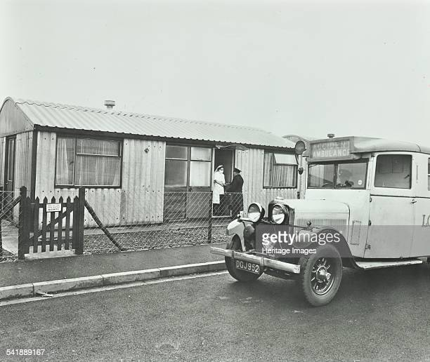 Ambulance delivering a gas and air cylinder Woolwich London 1946 The ambulance driver is handing over the cylinder of gas to a midwife at a...
