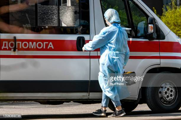 Ambulance doctor in protective suit as a measure against the coronavirus COVID19 near ambulance car on street in Kyiv Ukraine on April 03 2020