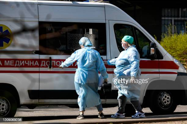 Ambulance doctors in protective suits as a measure against the coronavirus COVID19 near ambulance car on street in Kyiv Ukraine on April 03 2020