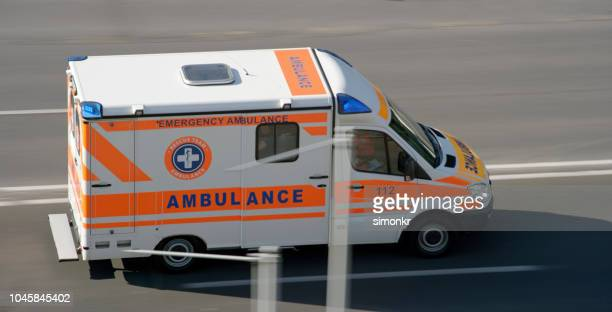 ambulance driving on road in city - ambulance stock pictures, royalty-free photos & images