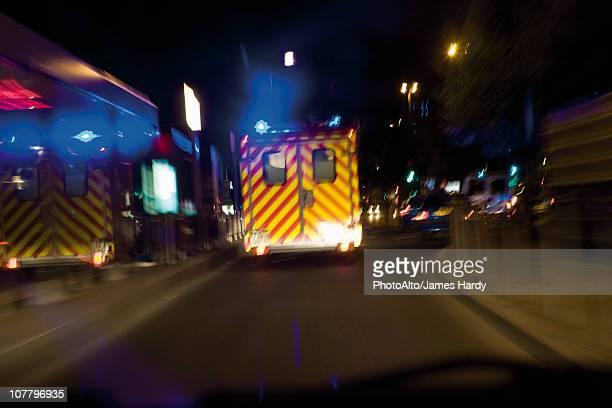 ambulance driving on street at night - frankreich stock-fotos und bilder