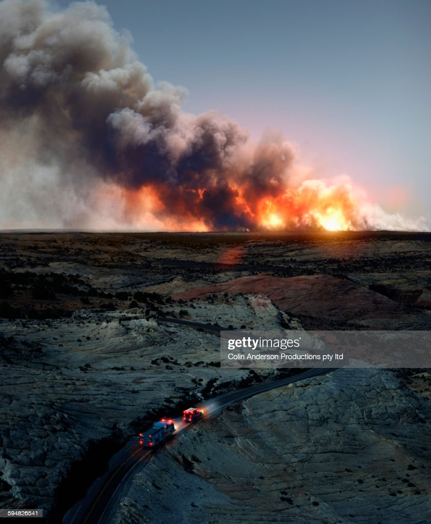 Ambulance driving to wildfire in desert : Stock Photo