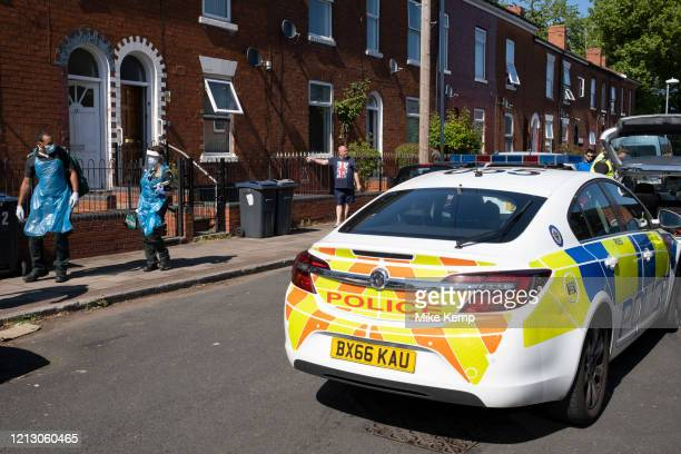 Ambulance health workers leave a home in full PPE after examining potential injuries on John Street in the inner city area of Lozells police chased a...