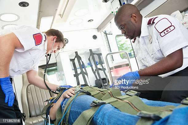 Ambulance medics helping injured girl on way to hospital