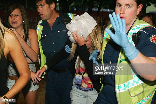 Ambulance officers escort a young school leaver during the Schoolies week celebrations in Surfers Paradise on November 23 2008 on the Gold Coast...
