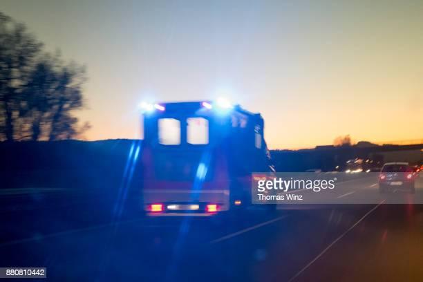 ambulance on freeway at dusk - rettung stock-fotos und bilder