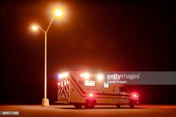 ambulance on road at night - ambulance stock pictures, royalty-free photos & images